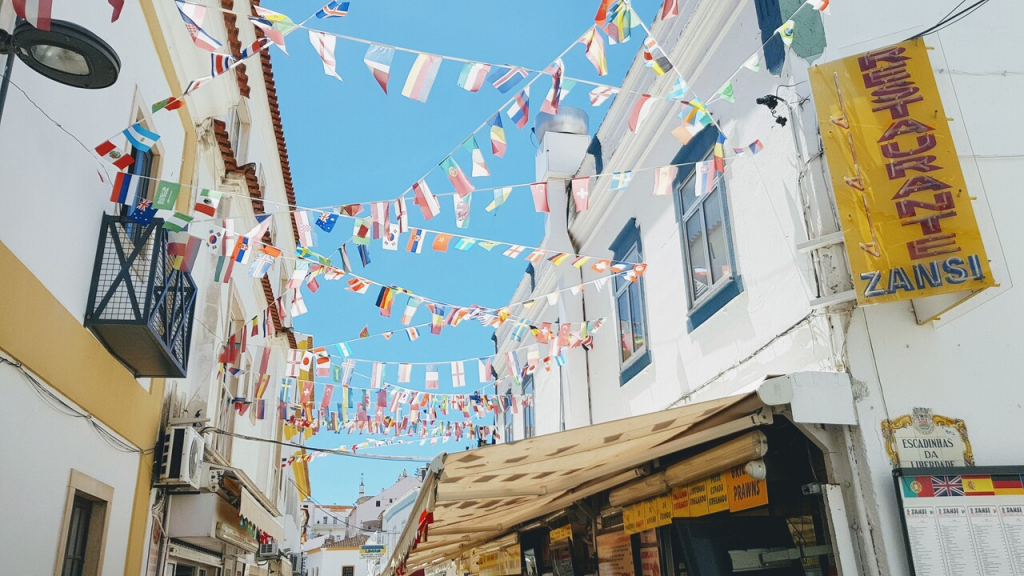 A narrow street with colourful flags from different countries hanging across the alley. A sign on the wall says Zansi. The sky is blue.